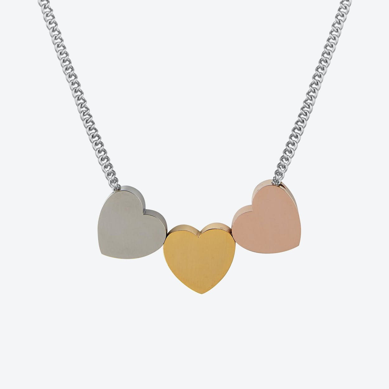 Candy Hearts Trio Necklace in One heart is finished in polished stainless steel in one in 18ct rose-gold plate and one in 18ct gold plate.